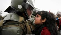 A demonstrator looks at a riot policeman during a protest marking the country's 1973 military coup in Santiago, Chile